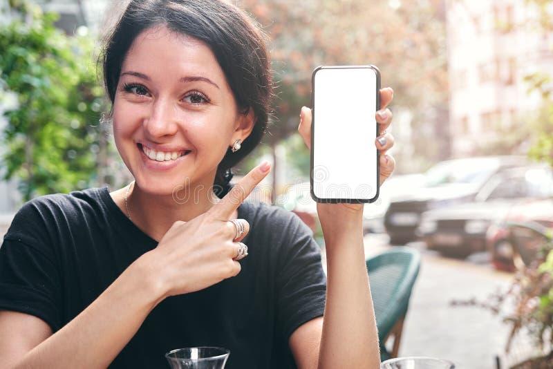 Gelukkige mooie vrouw die en mobiele telefoon met het lege witte scherm in koffie houden tonen stock foto's
