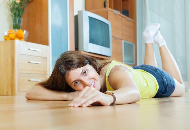Gelukkige mooie vrouw op parketvloer stock foto