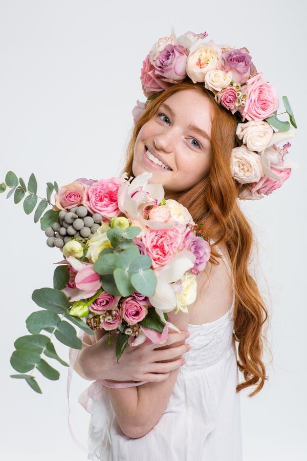 Gelukkige mooie vrouw in rozenkroon met boeket van bloemen stock foto's
