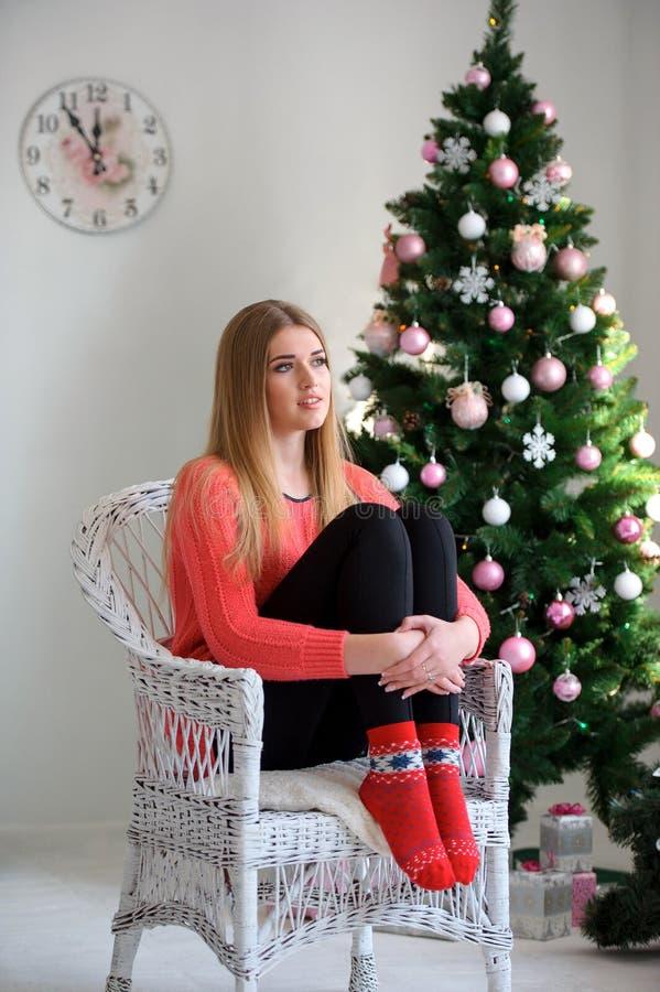 Gelukkige mooie vrouwenzitting als voorzitter tegen Kerstboom stock foto's
