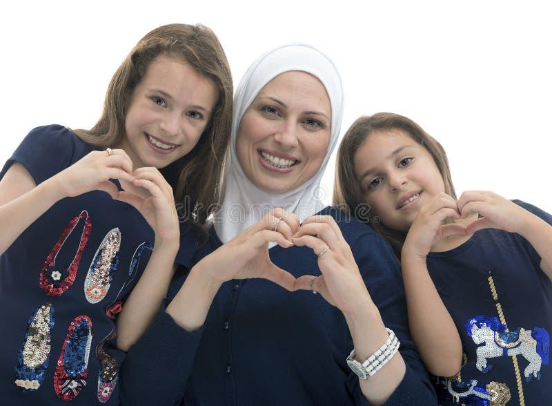 Gelukkige Moslim Vrouwelijke Familie, Moeder en Haar Dochters met Handgebaar van het Teken van de Hartliefde stock foto's