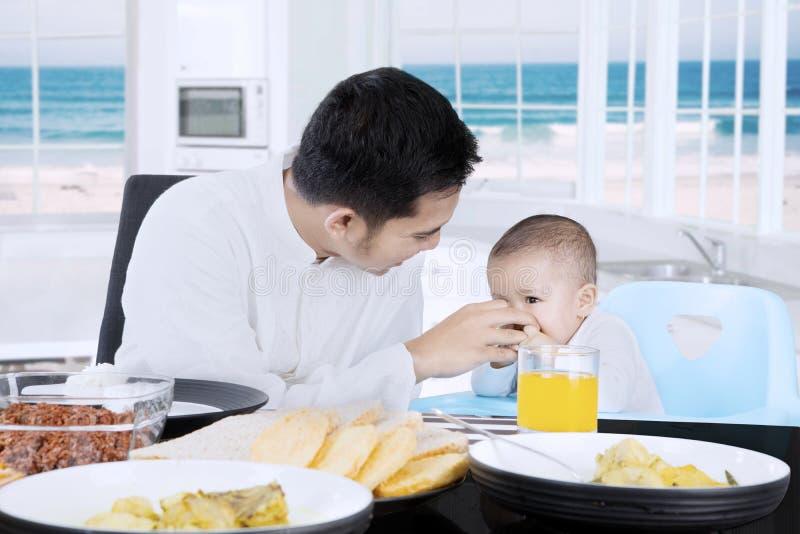 Gelukkige moslimvader die zijn baby voeden stock foto's