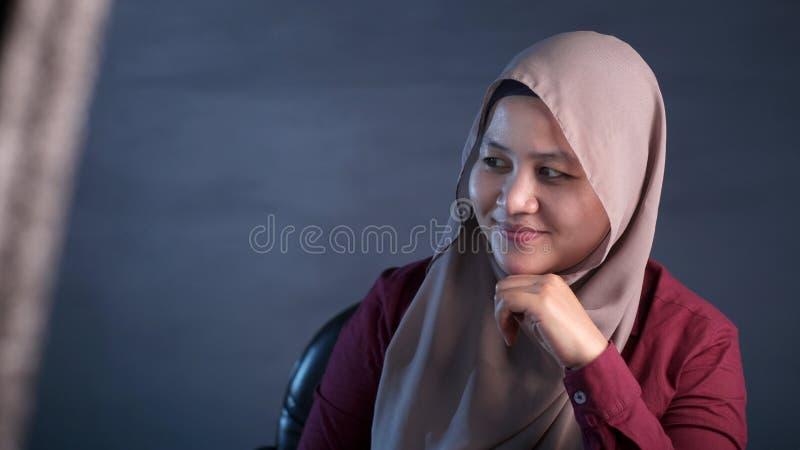Gelukkige Moslimvrouw die met het Denken Uitdrukking glimlachen stock foto