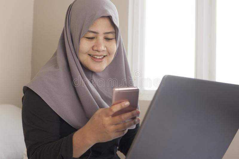 Gelukkige Moslimvrouw die met Laptop en Smartphone in Haar Slaapkamer werken stock afbeeldingen