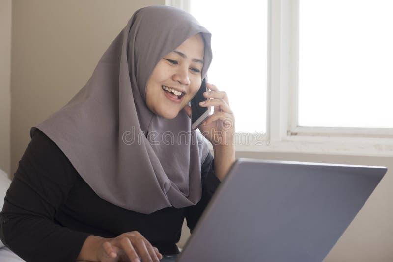 Gelukkige Moslimvrouw die met Laptop en Smartphone in Haar Slaapkamer werken stock foto's