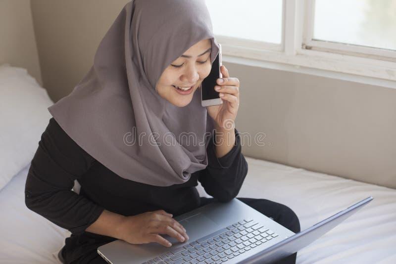 Gelukkige Moslimvrouw die met Laptop en Smartphone in Haar Slaapkamer werken royalty-vrije stock fotografie