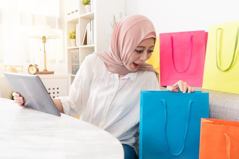 Gelukkige moslimvrouw die mobiel digitaal tabletstootkussen gebruiken stock fotografie