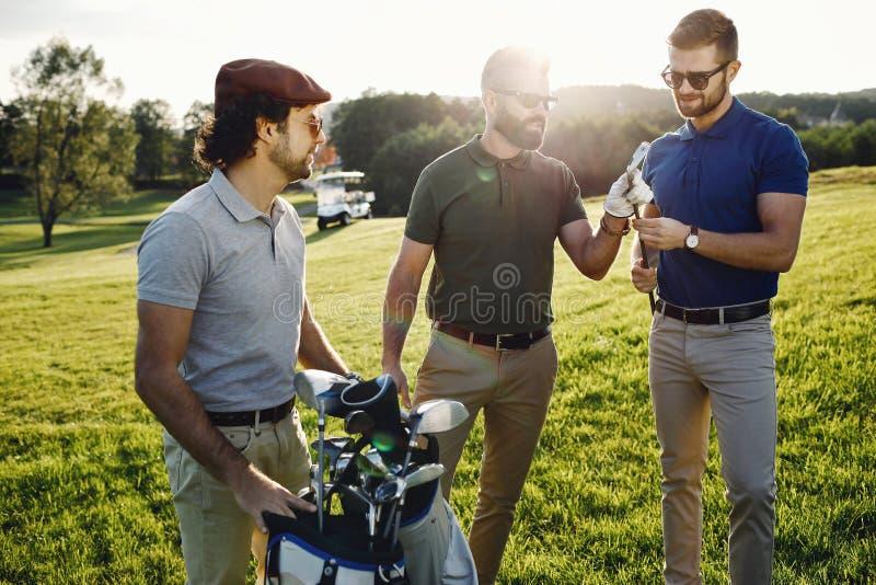 Gelukkige multi-etnische golfspelers die tijd samen in golfcursus doorbrengen stock foto