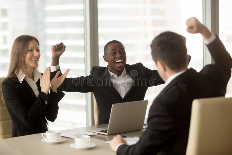 Gelukkige multi-etnische het commerciële team vieren overwinning, die Ha opheffen stock foto
