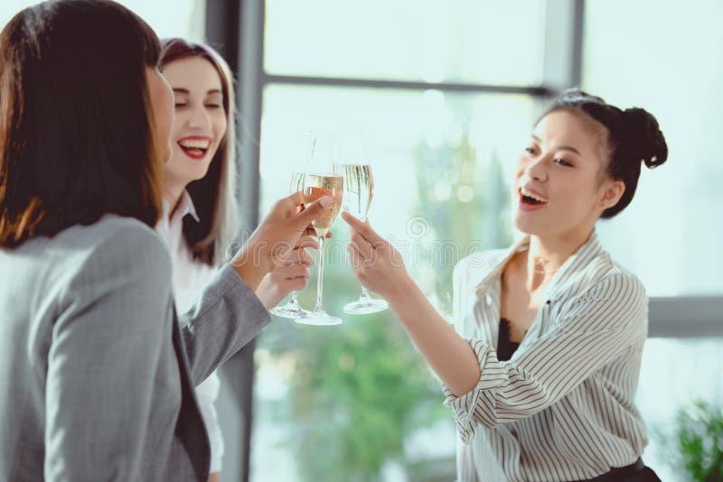 gelukkige multi-etnische onderneemsters die met champagneglazen clinking stock foto