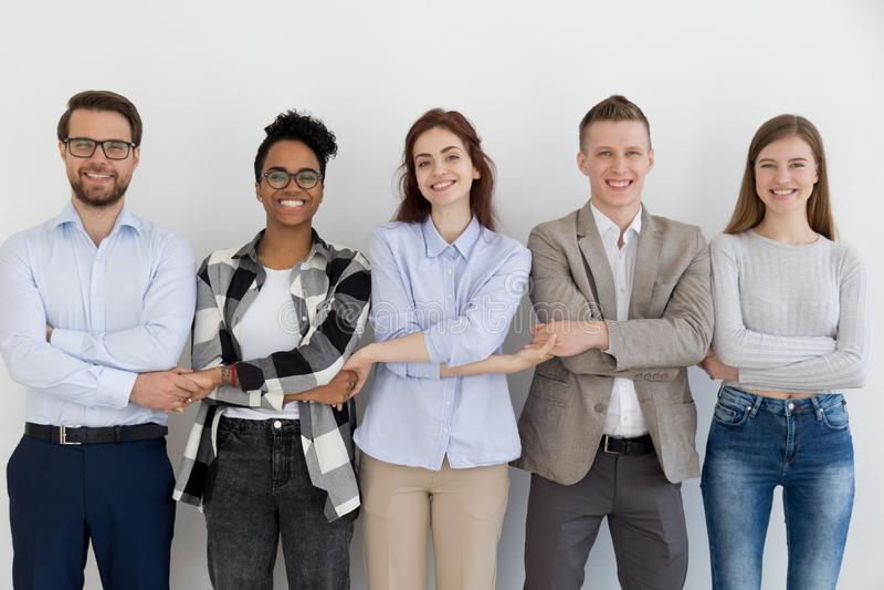 Gelukkige multi-etnische teammensen handen houden die zich bevindt in rij stock fotografie