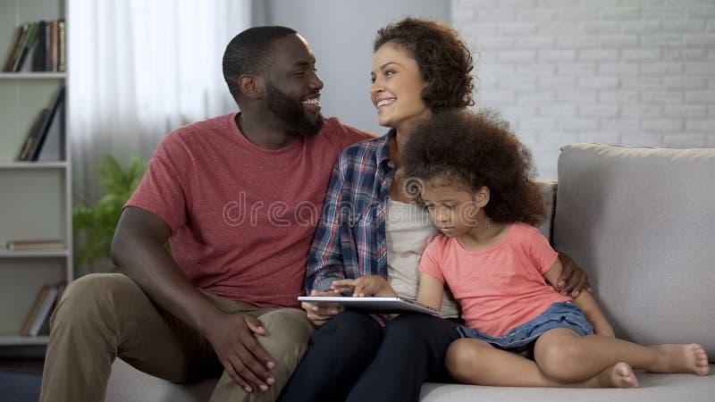 Gelukkige multiraciale geboortenregelingreis voor vakantie, die online op tablet boeken stock afbeelding