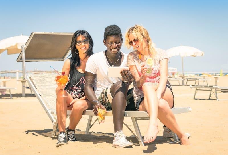 Gelukkige multiraciale meisjesvrienden die cocktails met tablet drinken royalty-vrije stock afbeeldingen