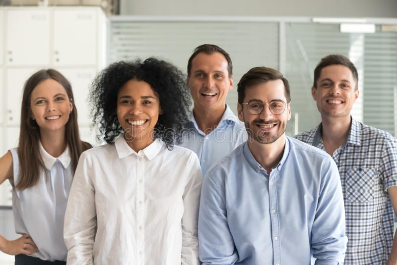 Gelukkige multiraciale professionele werknemers die camera, team bekijken royalty-vrije stock foto's