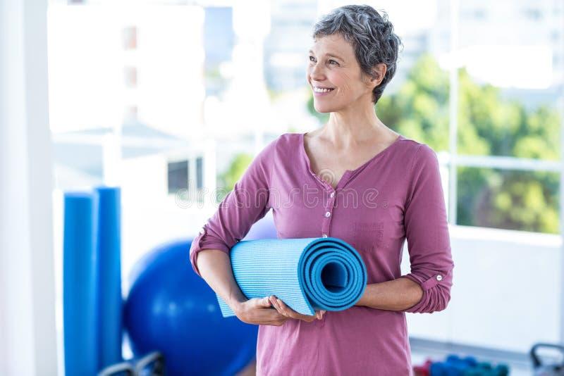 Gelukkige nadenkende rijpe vrouw met yogamat stock afbeeldingen