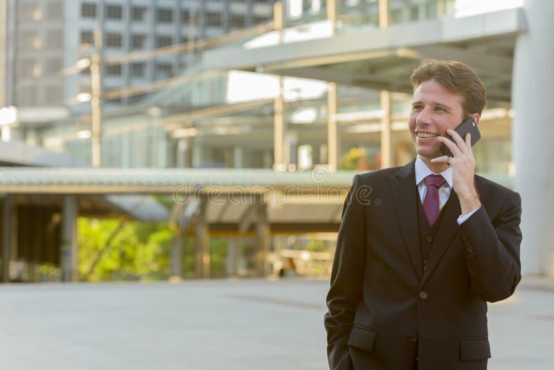 Gelukkige nadenkende zakenman die en op mobiele telefoon glimlachen spreken stock foto