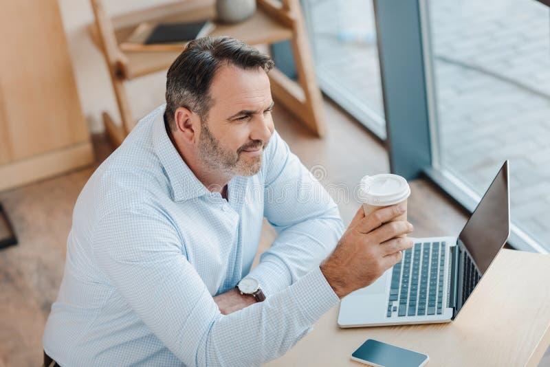gelukkige nadenkende zakenman met beschikbare kop van koffie en laptop royalty-vrije stock afbeeldingen