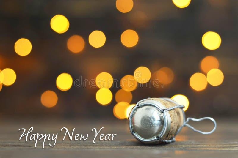 Gelukkige nieuwe jaarkaart Champagne-cork op houten achtergrond stock afbeelding