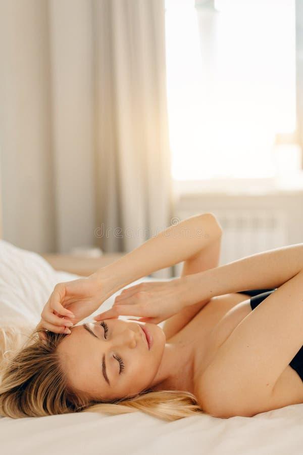 Gelukkige ochtend Het glimlachen van vrij het jonge blondevrouw ontspannen in wit bed royalty-vrije stock foto