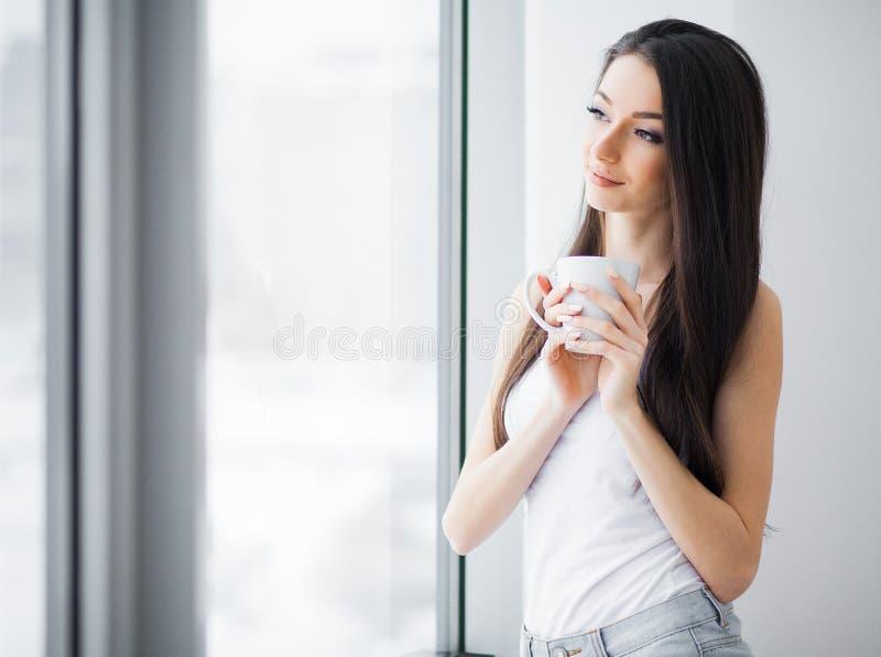 Gelukkige ochtend Het portret van mooie jonge vrouw status bij venster, het drinken koffie en het kijken buitenkant geniet van va royalty-vrije stock foto