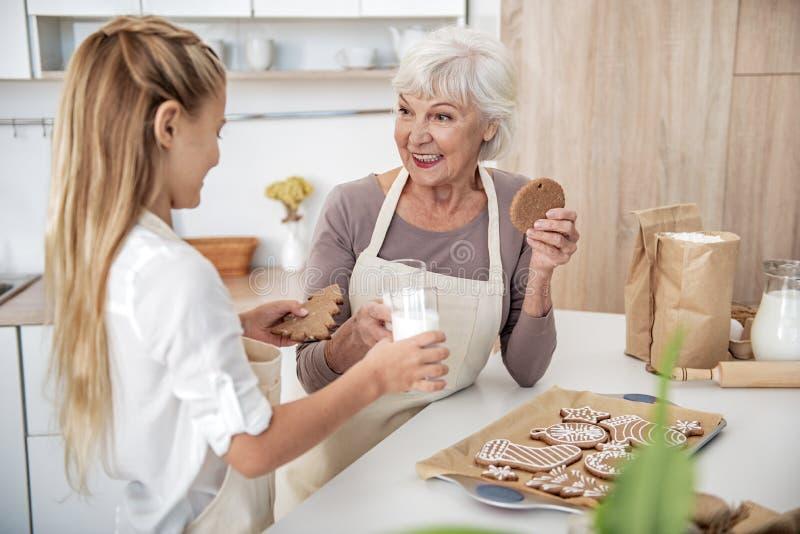 Gelukkige oma die gebakken zoet gebakje met kleindochter eten stock afbeeldingen