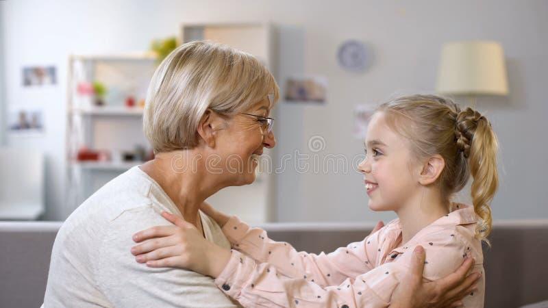 Gelukkige oma en kleindochter die en elkaar omhelzen bekijken samenhorigheid royalty-vrije stock foto