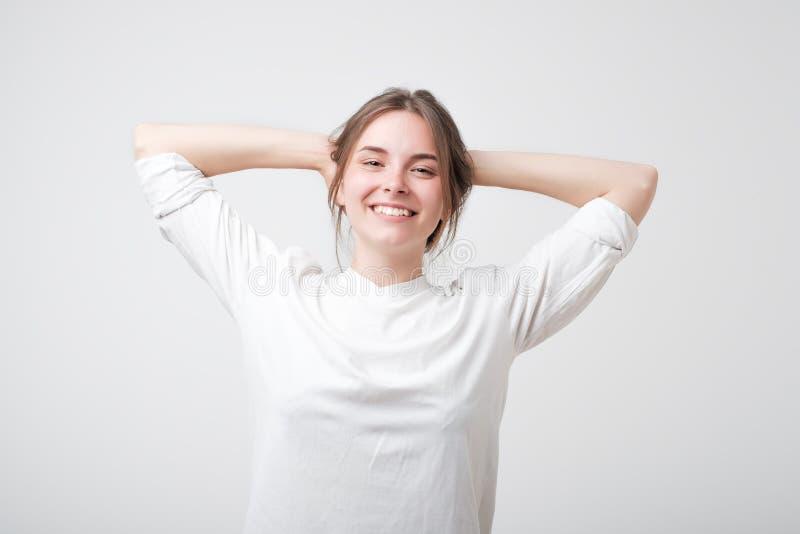 Gelukkige onbezorgde jonge Kaukasische vrouw in witte t-shirt met het leuke grijns stellen met haar handen over haar hoofd royalty-vrije stock afbeeldingen