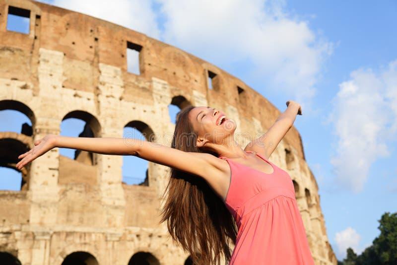 Gelukkige onbezorgde verrukte reisvrouw door Colosseum stock foto