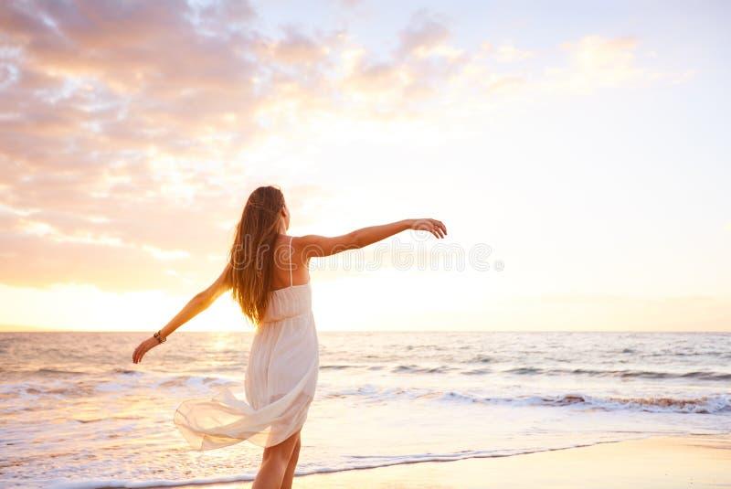 Gelukkige Onbezorgde Vrouw die op het Strand bij Zonsondergang dansen royalty-vrije stock fotografie