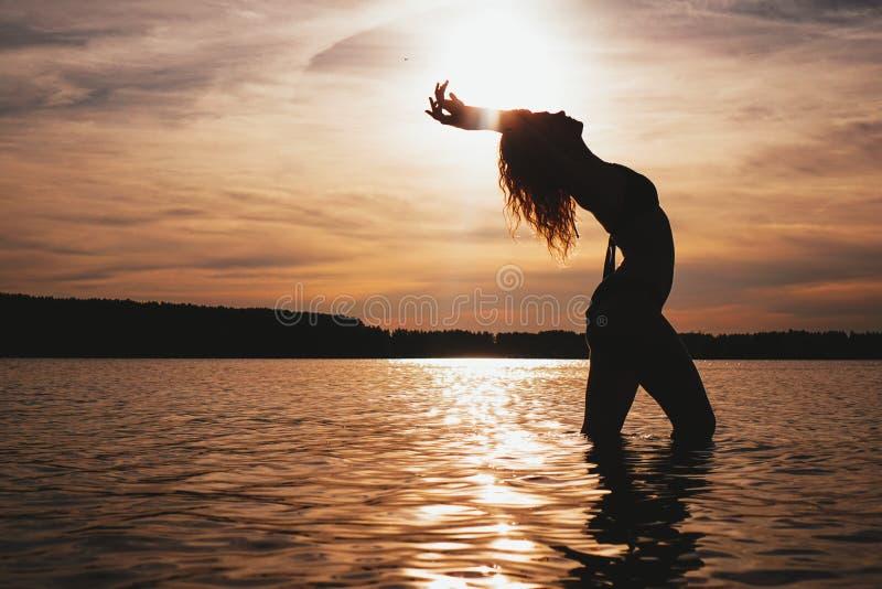 Gelukkige Onbezorgde Vrouw die van Mooie Zonsondergang op het Strand genieten royalty-vrije stock afbeeldingen