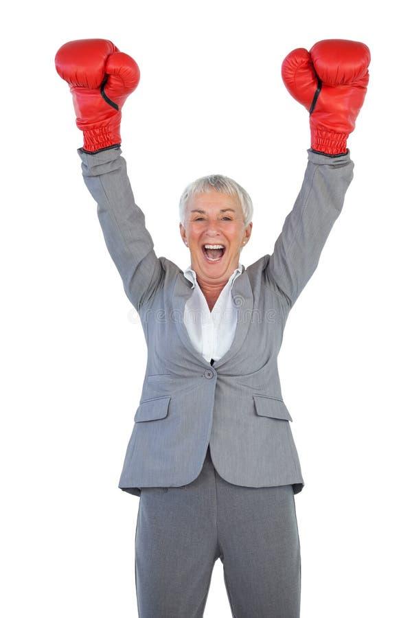 Gelukkige onderneemster die bokshandschoenen dragen en opheffend haar wapens royalty-vrije stock foto
