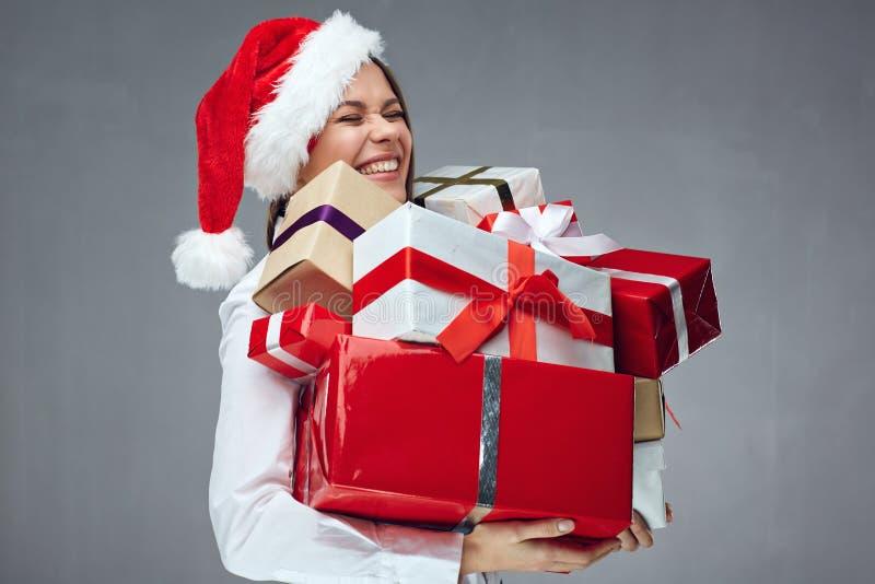 Gelukkige onderneemster die de holdingshoop van de Kerstmanhoed van Kerstmis dragen stock foto's