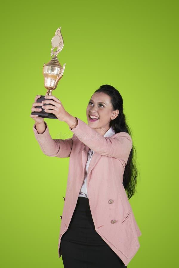 Gelukkige onderneemster die een trofee op studio opheffen royalty-vrije stock afbeeldingen