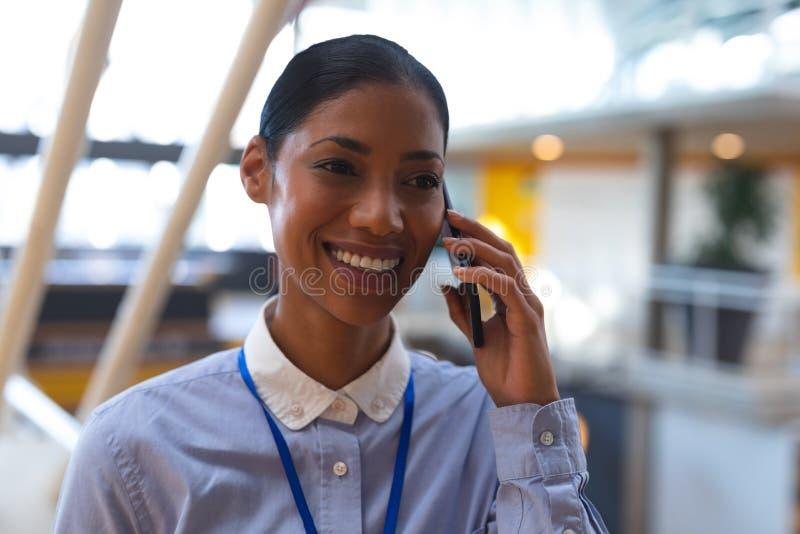 Gelukkige onderneemster die op mobiele telefoon in een modern bureau spreken stock afbeelding