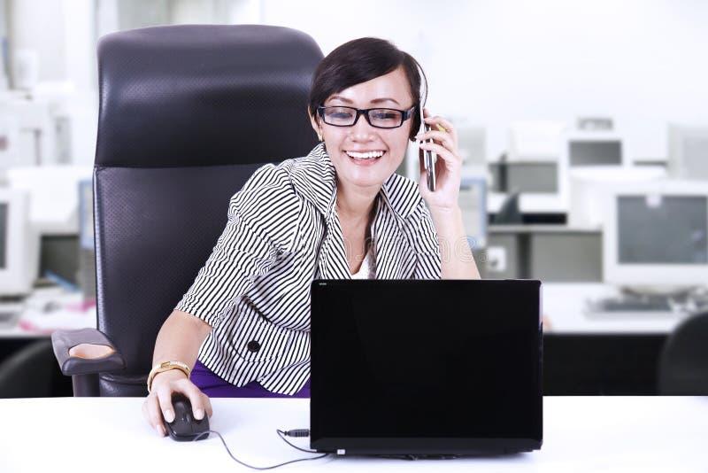 Gelukkige onderneemster die op telefoon op kantoor babbelen royalty-vrije stock fotografie