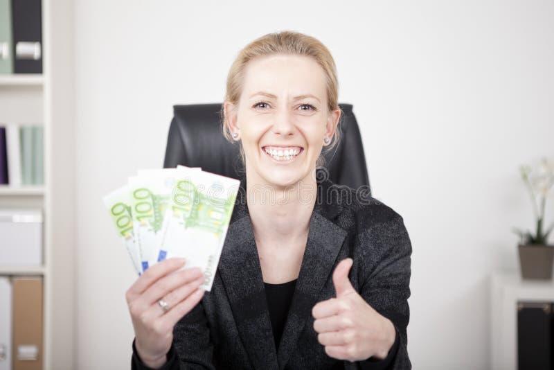 Gelukkige Onderneemster in Duimen op Holdingscontant geld stock afbeeldingen