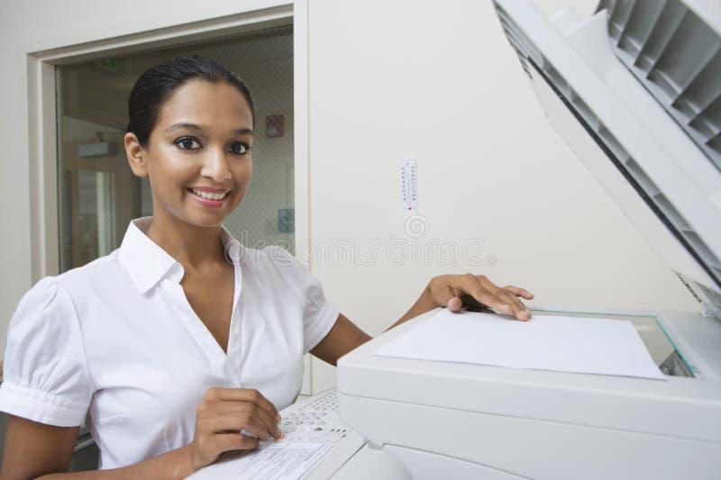 Gelukkige Onderneemster Using Fax Machine In Office royalty-vrije stock foto