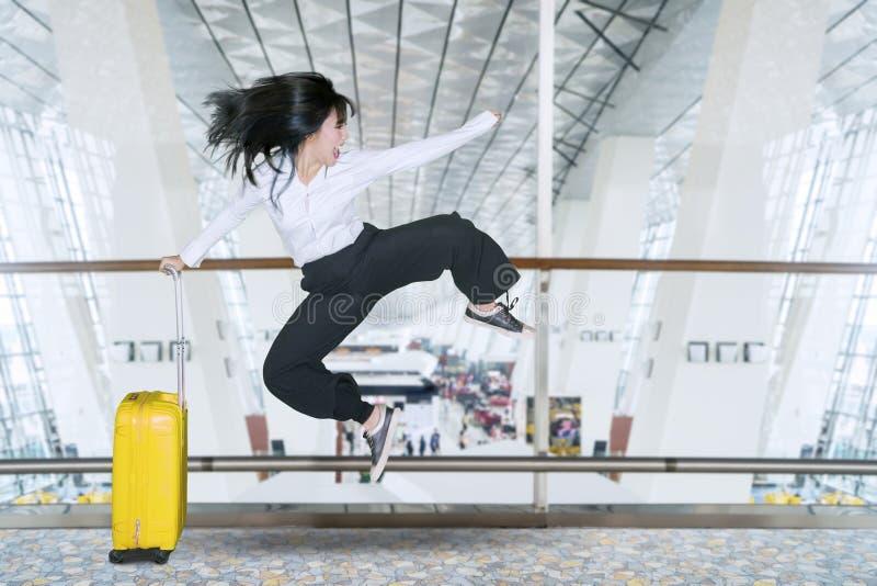 Gelukkige onderneemstersprongen in de luchthaven stock afbeeldingen