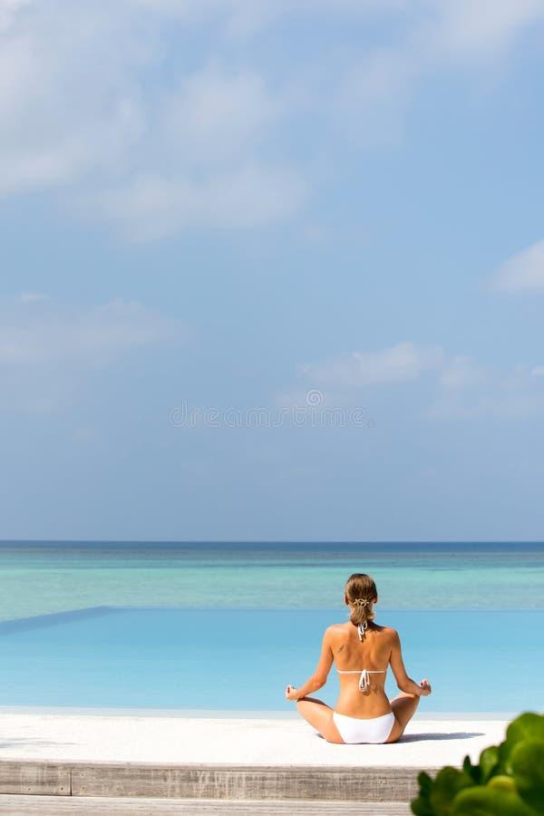 Gelukkige ontspannen jonge vrouw het praktizeren yoga in openlucht bij wit strand royalty-vrije stock fotografie