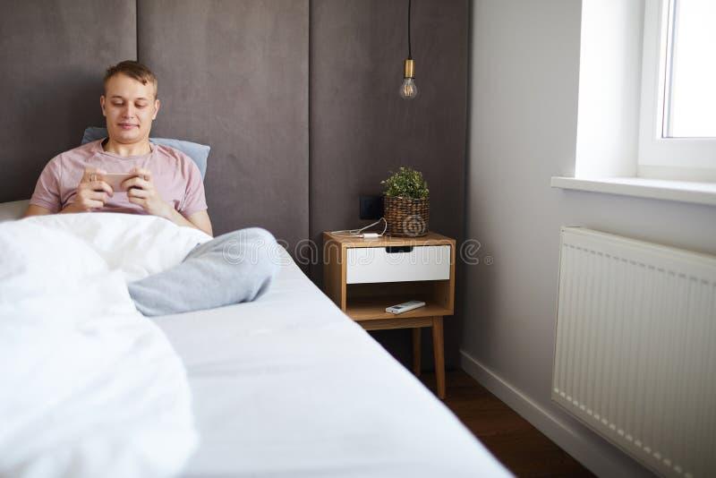 Gelukkige ontspannen kerel die op nieuwsgierige video in smartphone in bed letten royalty-vrije stock foto