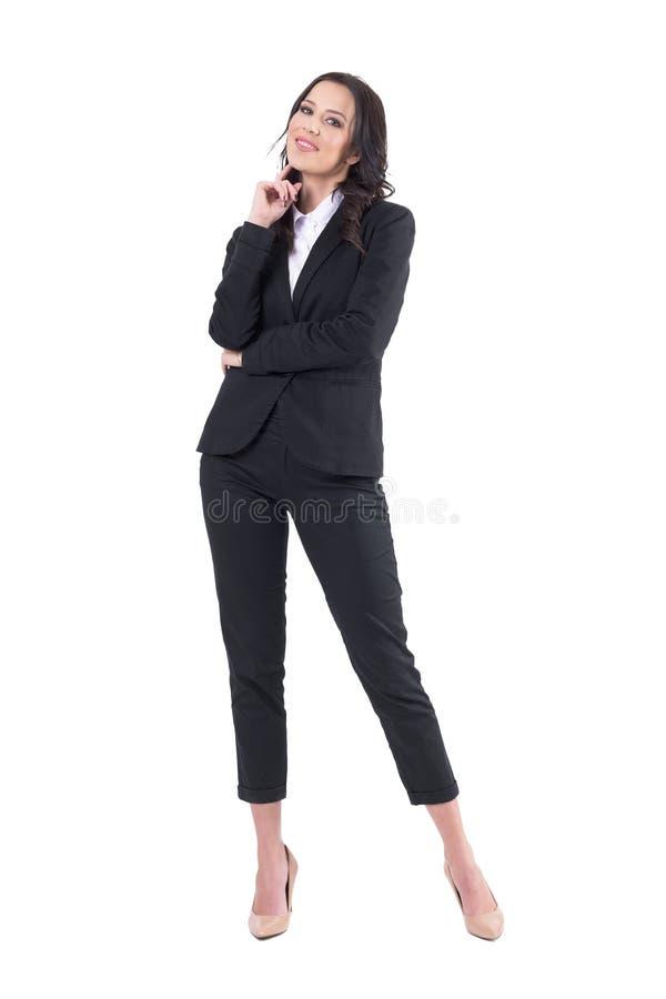 Gelukkige ontspannen mooie bedrijfsvrouw die in zwart formeel kostuum met hand op kin glimlachen royalty-vrije stock foto