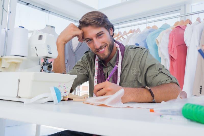 Gelukkige ontwerper die bij zijn bureau werken stock afbeeldingen
