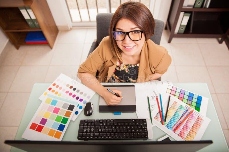 Gelukkige ontwerper die van haar baan houden stock foto's