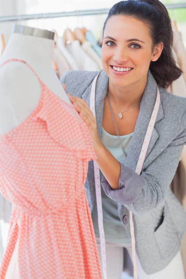 Gelukkige ontwerper het bevestigen kleding op een ledenpop royalty-vrije stock fotografie