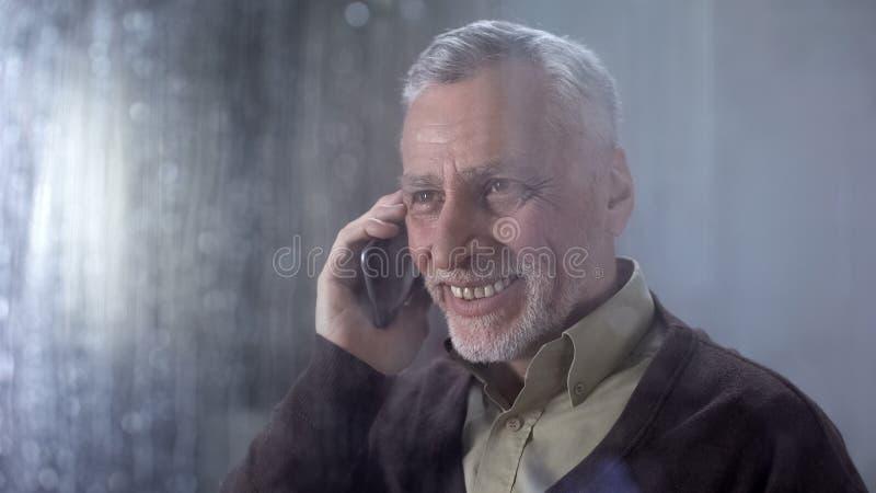 Gelukkige op telefoon spreken en grootvader die, familiemededeling, mobiele toepassing glimlachen royalty-vrije stock fotografie