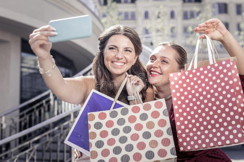 Gelukkige opgetogen vrouwen die hun het winkelen zakken tonen royalty-vrije stock fotografie
