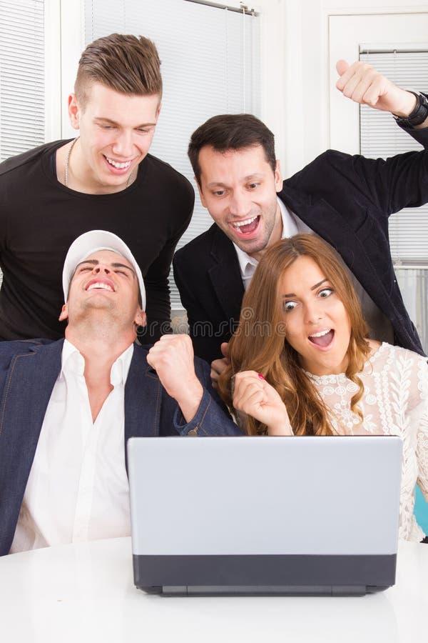 Gelukkige opgewekte bedrijfsmensen die online het bekijken laptop c winnen royalty-vrije stock afbeeldingen