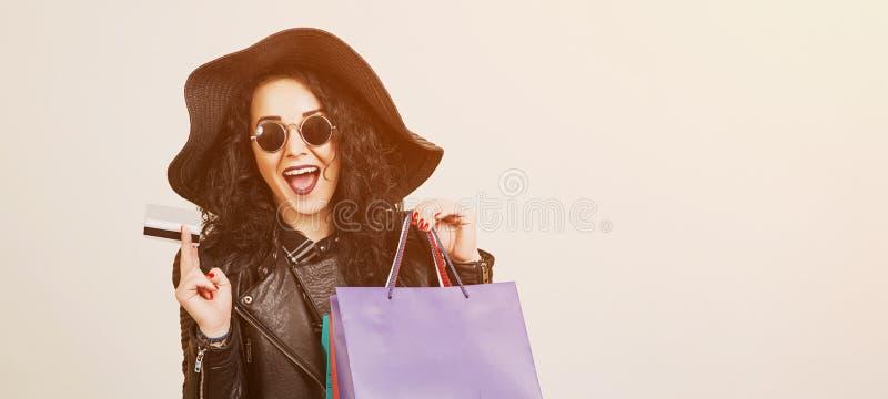 Gelukkige opgewekte hipster vrouw die in zonnebril creditcard en kleurrijke het winkelen zakken houden ? heerful vrouw die camera royalty-vrije stock foto