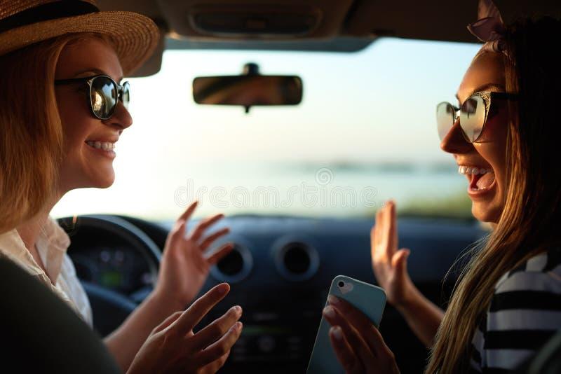Gelukkige opgewekte jonge vrouwen die in auto drijven en hoog gebaar vijf op de reis van de de zomervakantie maken Twee meisjes v royalty-vrije stock fotografie