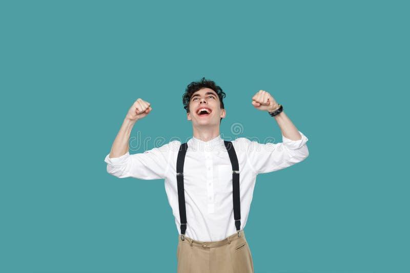 Gelukkige opgewekte mens die zijn overwinning vieren stock afbeelding